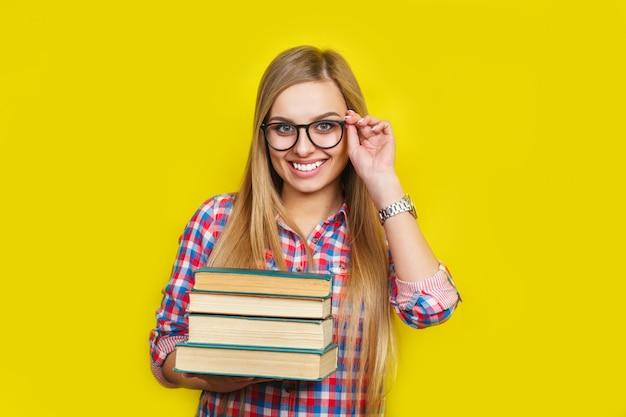 笑顔の若いスタイリッシュな学生はメガネとカジュアルな明るい衣装で黄色の壁の本に立っています。