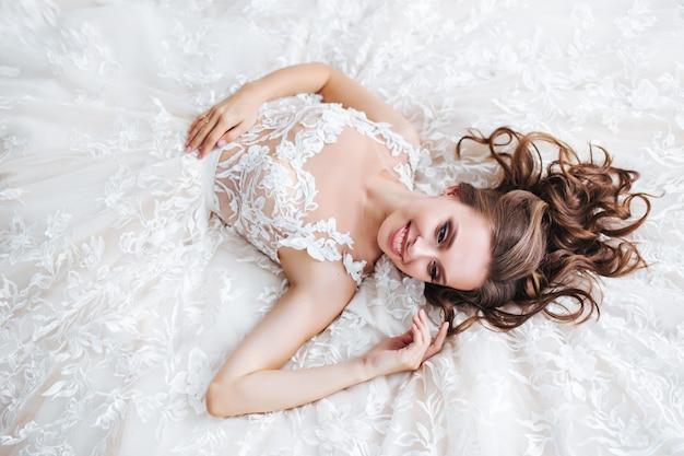 Красивая невеста лежит на белой кровати в отеле. женщина в белом платье отдыхает в спальне