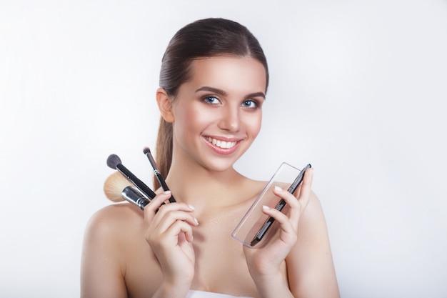 化粧ブラシと白い壁にアイシャドウと美しい若い笑顔の女性モデルのクローズアップ。