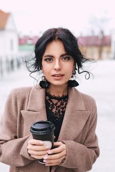 紙のコーヒーカップを保持していると街で散歩を楽しんでいる美しい女性