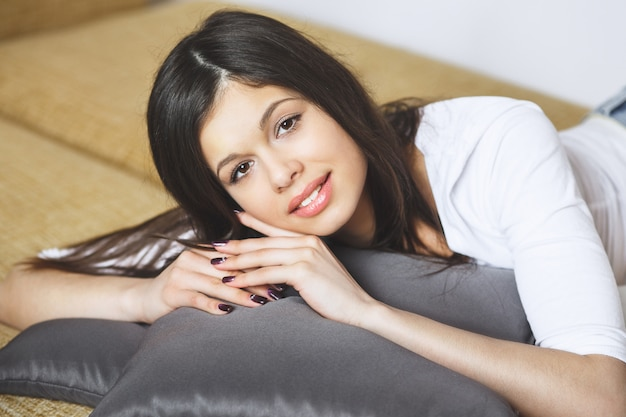 Расслабляющая женщина сидит удобно в диван-кресло, улыбаясь счастливым, глядя на камеру