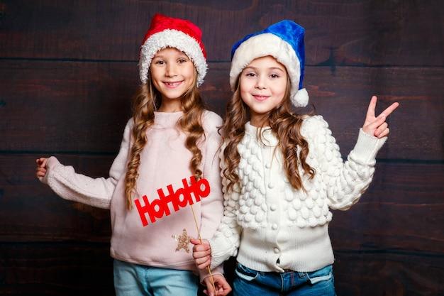 Улыбающиеся смешные сестры в новогодней шапке на деревянном фоне