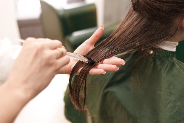 Парикмахер наносит маску для волос женщине в салоне красоты. процедура выпрямления волос ботоксом и кератином