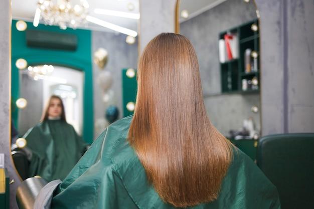 Блестящие и прямые волосы молодой девушки после процедуры ламинирования волос. кератиновые и ботоксные волосы