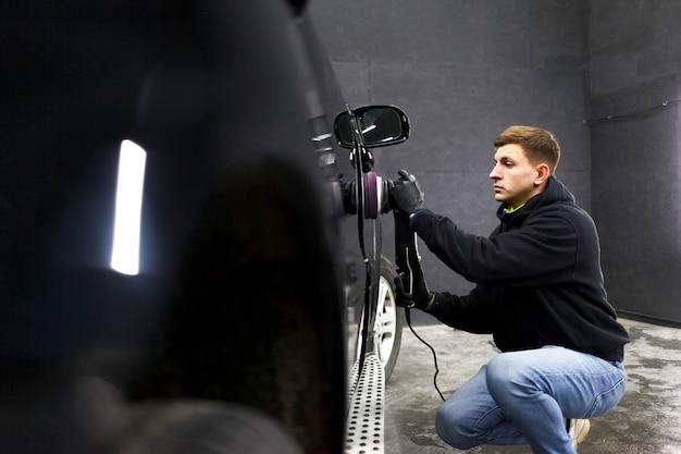 Работник центра детализации полирует кузов автомобиля