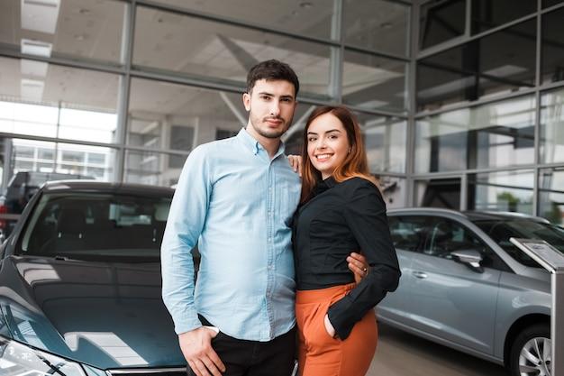 彼らの新しい自動車の近くの自動車販売店でのカップル
