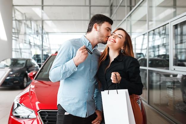 Счастливая пара в автосалоне купила новую машину
