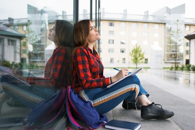 大学の建物に座っている学生