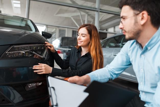 セールスマンは若いクライアントに車を見せます