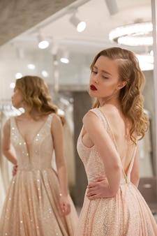 Девушка позирует в магазине свадебного платья