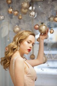 クリスマスボールの美しいドレスの女の子