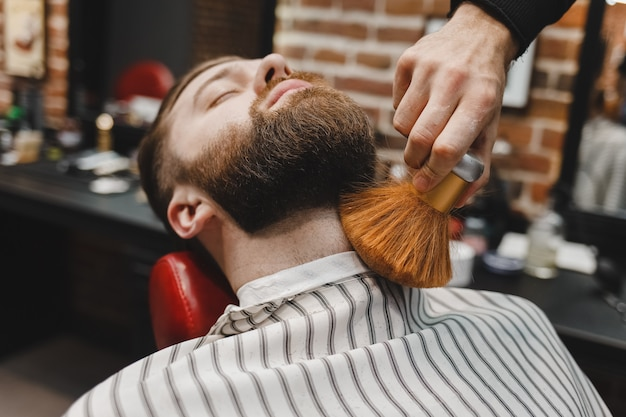 Парикмахер удаляет волосы с бороды клиента