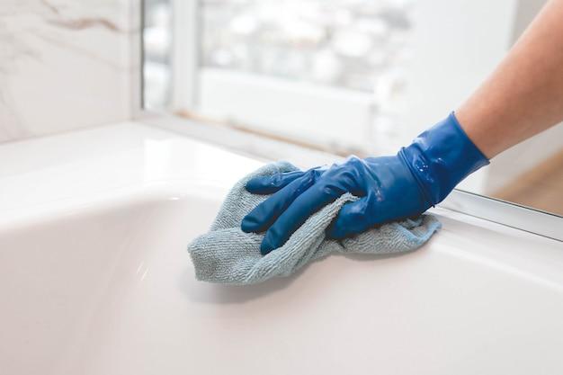 Домохозяйка в перчатках моет ванную комнату