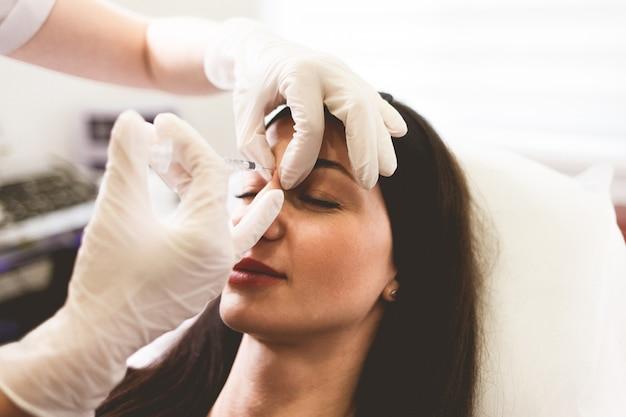 美容師医師がボトックスを患者の額に注入します
