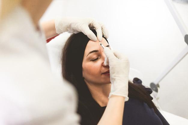 Врач-косметолог вводит ботокс в лоб пациента