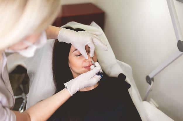 Женщина делает инъекцию красоты в нос.