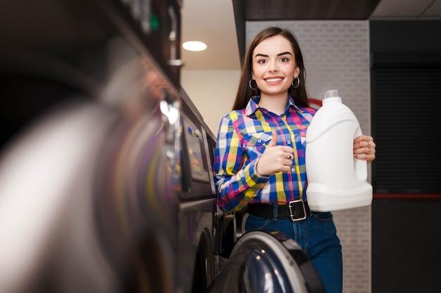 Молодая женщина рекомендует моющее средство, держа бутылку в руке и показывая большой палец вверх.