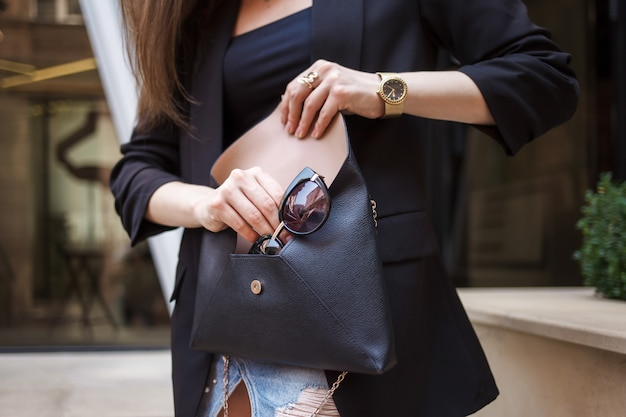 女の子はバッグから眼鏡を取り出します。スタイリッシュな女性は彼女のバッグに眼鏡をかける