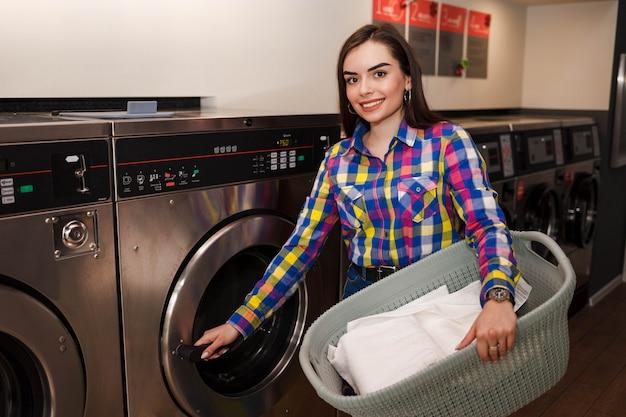 Девушка с корзиной белья открывает дверцу стиральной машины в общественной прачечной