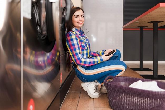 Позитивная женщина ждет конца стирки, сидя на полу в прачечной