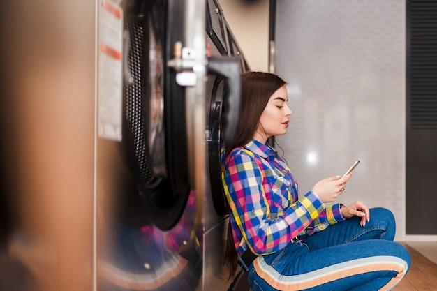Девушка сидит на полу в прачечной самообслуживания и слушает музыку в наушниках