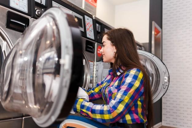 女の子は洗濯機に洗濯物をロードします。コインランドリーの女性