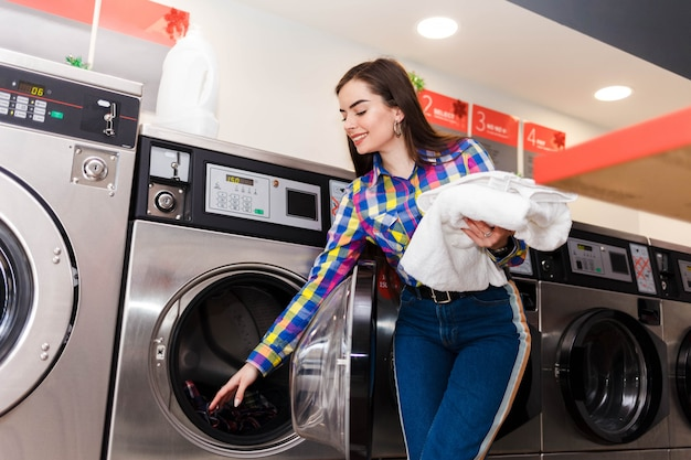 若い女の子は洗濯機から洗濯物を取り出します