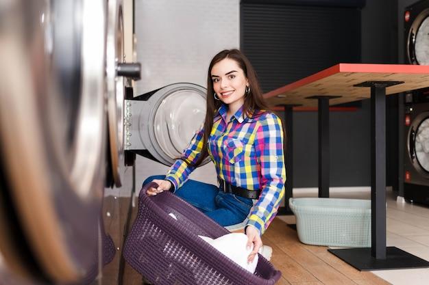 女の子は洗濯機に洗濯物をロードします。