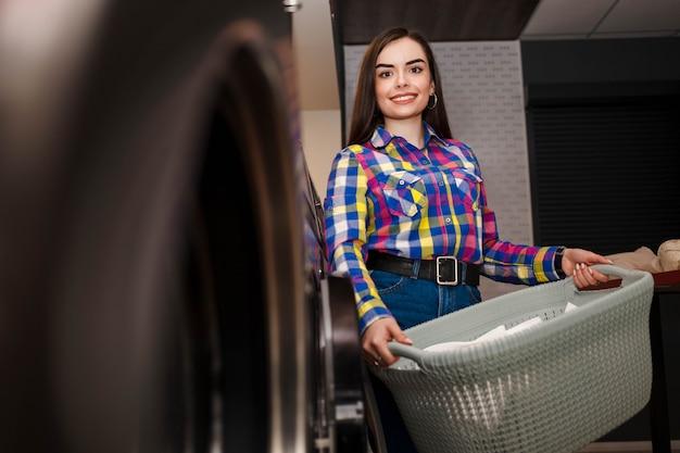 Улыбающаяся девушка стоит в прачечной самообслуживания и держит корзину с бельем