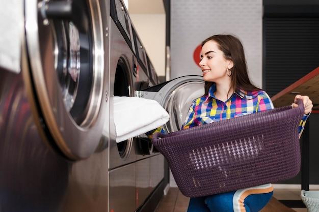 Девушка загружает белье в стиральную машину. женщина в общественной прачечной