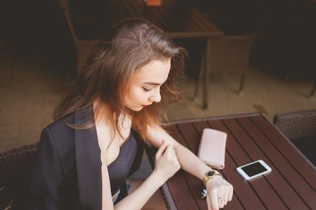 Бизнес женщина сидит в одиночестве за столом ресторана, глядя на часы