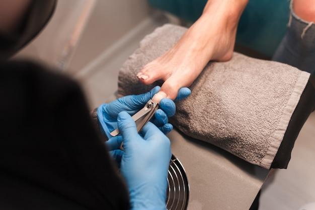 Педикюр подстригает ногти маникюрными ножницами