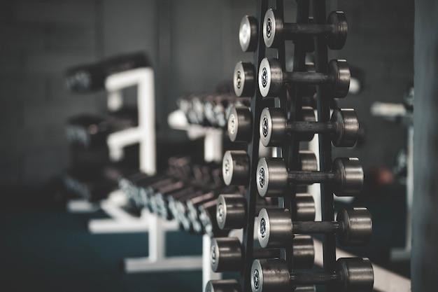 Стенд с гантелями в тренажерном зале, гантели установлены. много гантелей в фитнес клубе