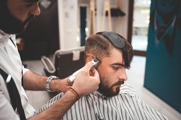 Парикмахер тщательно ориентируется на стрижку клиента.