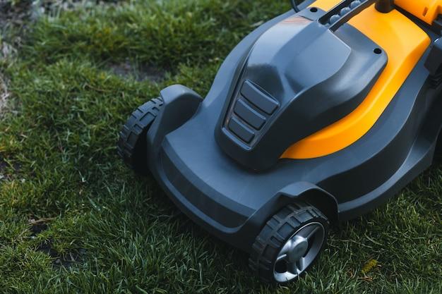 庭の芝生の上の電気芝刈り機