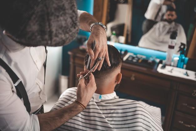 理髪店でハサミで散髪をしているプロの美容師