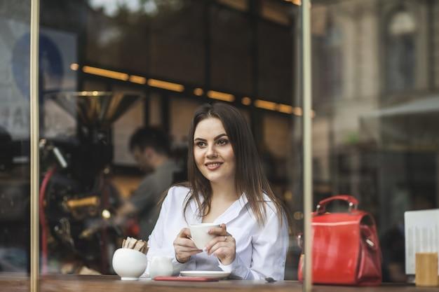Женщина держит чашку горячего кофе в руках