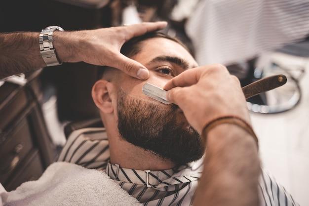 Парикмахерская бреет бороду клиента