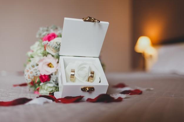 Букет и коробка с обручальными кольцами в постеле усыпанном лепестками роз