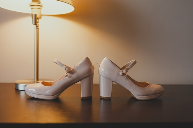 Обручальное кольцо лежит между туфлями невесты.