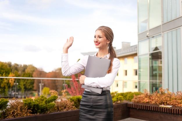 Молодой секретарь с папкой в руках машет. позитивная деловая женщина машет привет