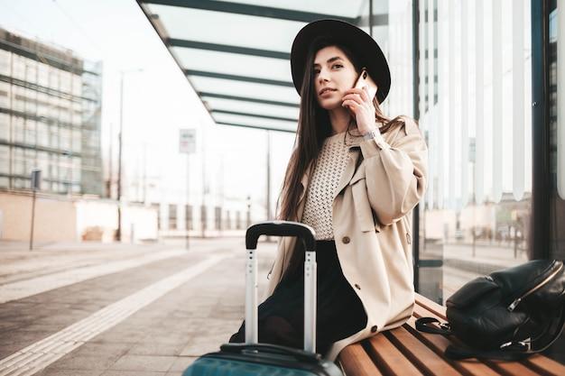 公共交通機関を待っているときに電話で話しているコートと帽子に身を包んだスタイリッシュな女の子