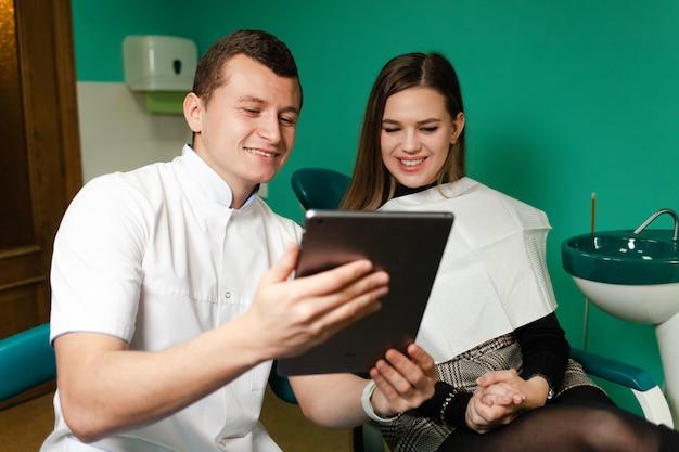 タブレットを持つ歯科医は、今後の治療に関する患者情報を表示します。口腔病学における現代技術。現代の歯科医のコンセプト