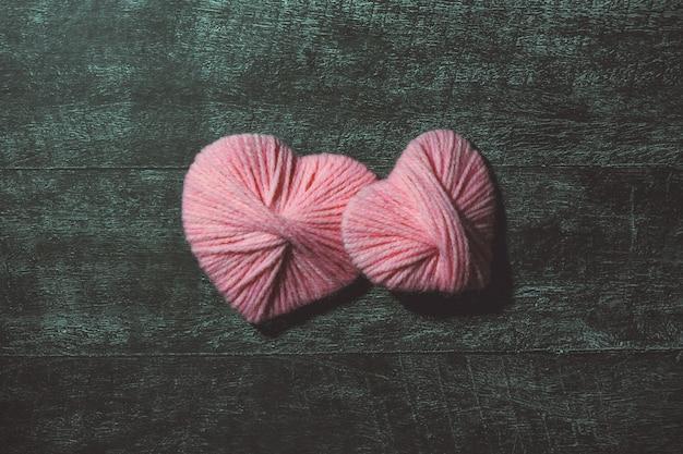聖バレンタインデー。手作りの暗い木製のテーブルにピンクの装飾的なスレッドハート。コンセプトが大好きです。グリーティングカード。コピースペース