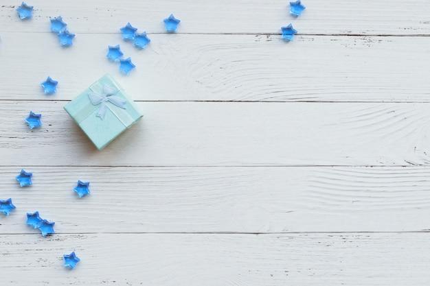 明るい青いギフトと白い木の板に青い星の装飾的組成物とクリスマスの背景。明けましておめでとうございます。コピースペース。