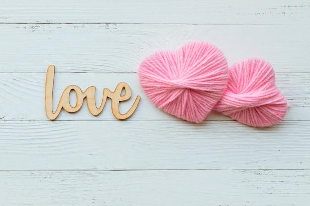 聖バレンタインデー。手作りの装飾的なスレッドピンクハートと木製の言葉。コンセプトが大好きです。コピースペース