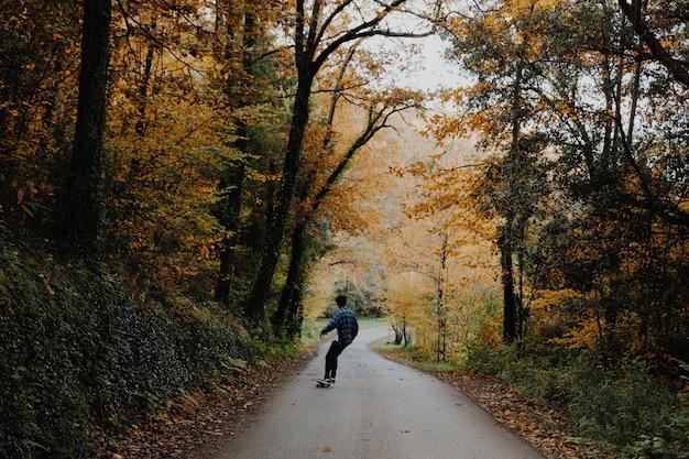 Молодой человек катается на скейтборде посреди леса осенью в каталонии