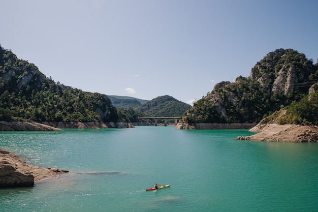 夏の山に囲まれた結晶の湖で晴れた日にカヤックをしている男性