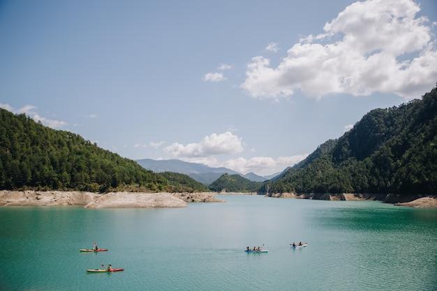 夏の晴れた日に山の青い水湖でカヤックをしている人々のグループ