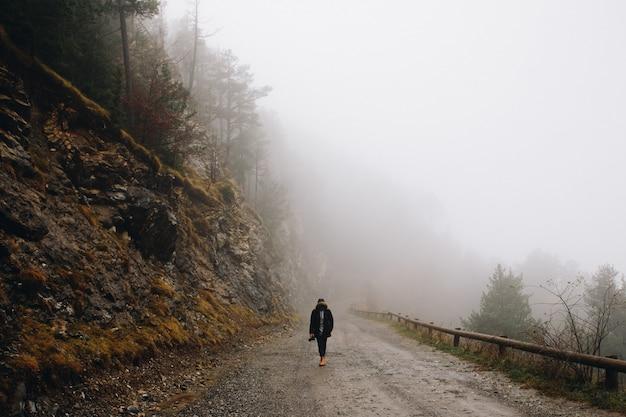 Человек идет в гору в туманный день в горах зимой